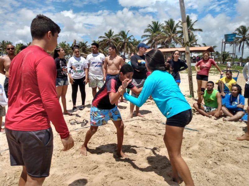 Meninos e meninas juntos na prática do Beach Wrestling